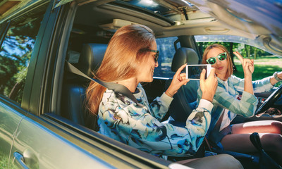Woman taking photo to her friend inside of car