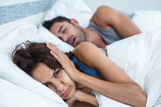 Woman blocking ears with hands while man snoring on bed