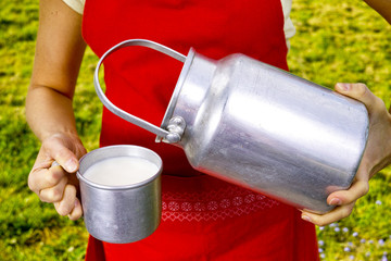 Young woman with fresh organic farm cowmilk in aluminum milk can