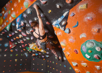 Strong female climber on boulder climbing wall indoor reaches the top