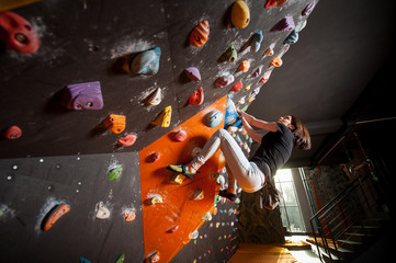 Climber sporty woman climbing on practice wall indoor, reaching next handhold