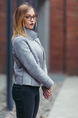 Young woman standing in front of office buildings