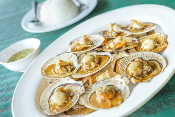 Baked scallops with butter and soy sauce in natural scallop shell delicious Thai sea food.