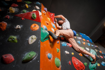 Male rock climber practicing artificial rock climbing on a rock wall indoors, with climbing shoes. Bouldering