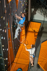Male climbing on an indoor rock-climbing wall, belayer standing on the ground belaying the climber