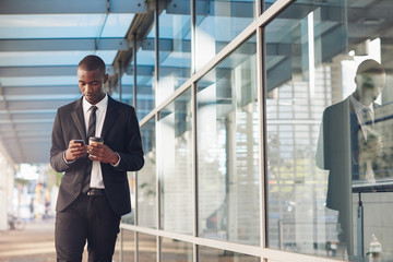 Young businessman of African descent reading a phone message out