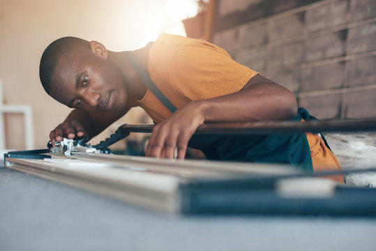 Contemporary young African artisan working with cutting tool