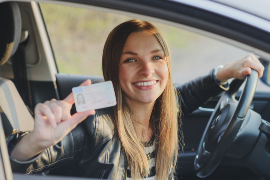 Attractive young woman proudly showing her drivers license