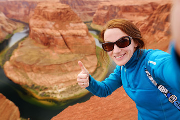 Young tourist taking a photo of herself by famous Horseshoe Bend, Arizona