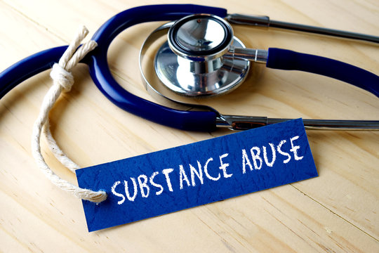 Medical conceptual image with SUBSTANCE ABUSE word written on label tag and stethoscope on wooden background.