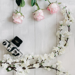 Vintage film camera, sakura branch, pink rose flowers on the white wooden desk. Top view, flat lay