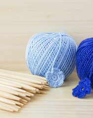 Blue balls of cotton yarn for knitting, crochet. Wooden needles, bamboo background