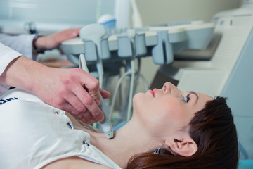 woman getting ultrasound of a thyroid from doctor