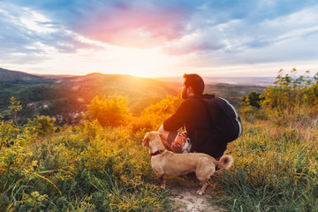 Man with dog enjoying mountain sunset