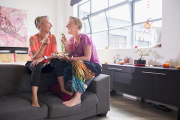 Caucasian lesbian couple eating on sofa