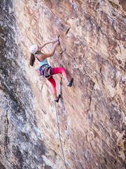Mixed race girl rock climbing on cliff