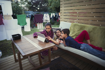 Mother and children using digital tablet in backyard