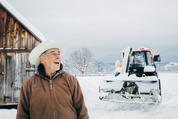 Caucasian farmer and tractor in snowy field