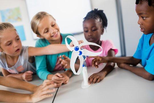 Pupils touching a wind turbine model