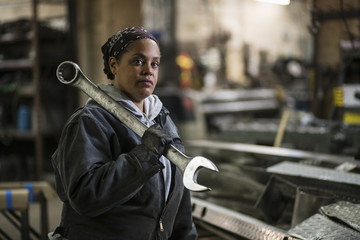 African American worker holding wrench in factory