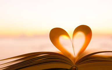 Heart shape from a book page against a beautiful sunrise.