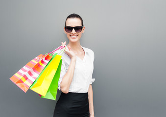 Happy young woman holding colorful shopping bags.