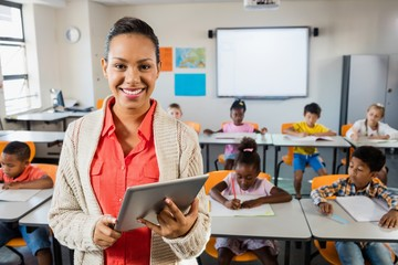 Miced race teacher posing in front of class with tablet pc