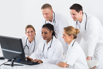 Group Of Doctors Looking At Computer At Desk