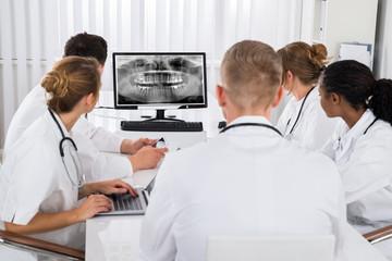 Doctors Looking At Teeth X-ray On Computer