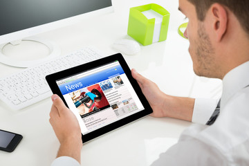 Man Reading News On His Digital Tablet
