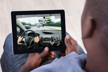 Man Playing Car Game On His Digital Tablet
