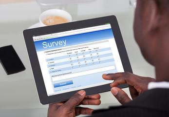 Businessperson Filling Survey Form On Digital Tablet