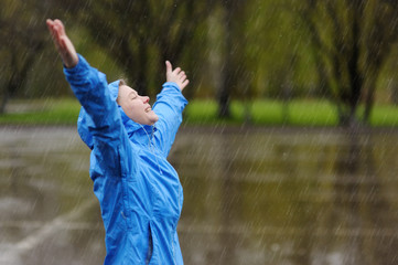 Happy woman standing with arms outstretched in rain.