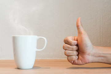 Close up of hand of man thumb up with a white cup of coffee.