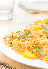 Pad Thai or Thai Fried Noodle on Wood Table with Glass Napkin Ch