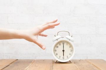 目覚まし時計と女性の手