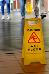 Warning sign for slippery floor with people legs in the backgrou