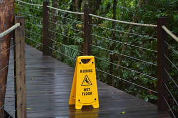 Warning sign for slippery floor on a wooden path of a rain fores