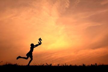 Silhouette children holding money in the sunset.
