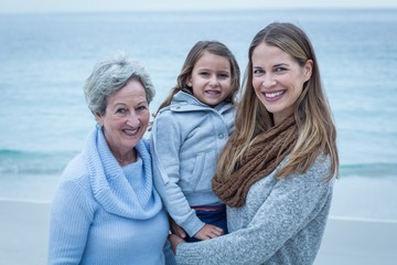 Happy three generations of women standing at beach