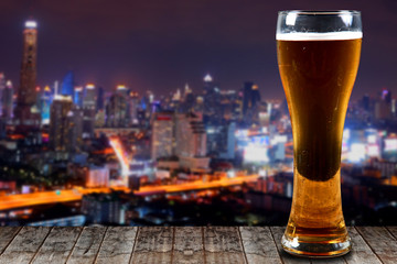 Glass of beer on a wooden City at night background.