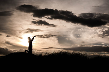 boy praying at sunset time, sihouette concept