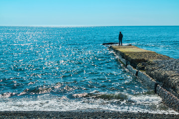 Breakwater with a silhouette of the person and pebble beach with sea views.