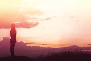 woman standing alone at the field during beautiful sunset