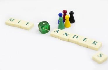 Eine Gruppe bunter Spielfiguren steht neben dem Wort: Miteinander! Ein Würfel liegt daneben. Sinnbild für eine vielfältige, funktionierende Gesellschaft.