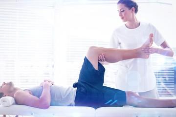 Composite image of physiotherapist massaging leg of man