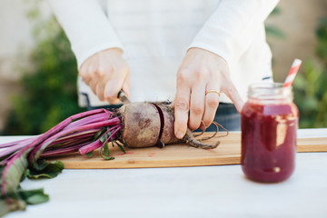 Close-up of hands preparing a beet juice