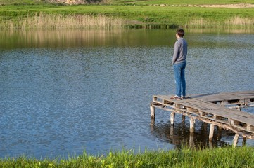 Man standing on the pier of a pond