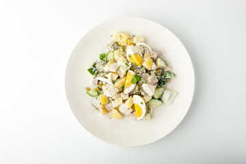 Olivier salad in ceramic plate on white background