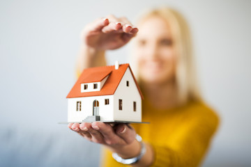 Home insurance concept - young woman holding home figurine